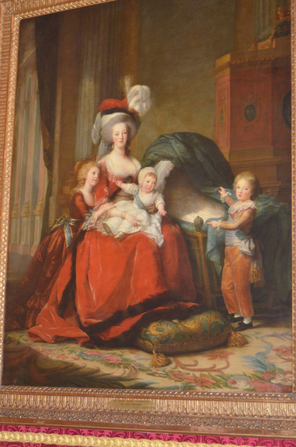 portrait of Marie Antoinette and her children. In the bassinet there was originally her baby painted, but she had the artist paint over it half way through because the baby died. In the right lighting you can still see the baby!